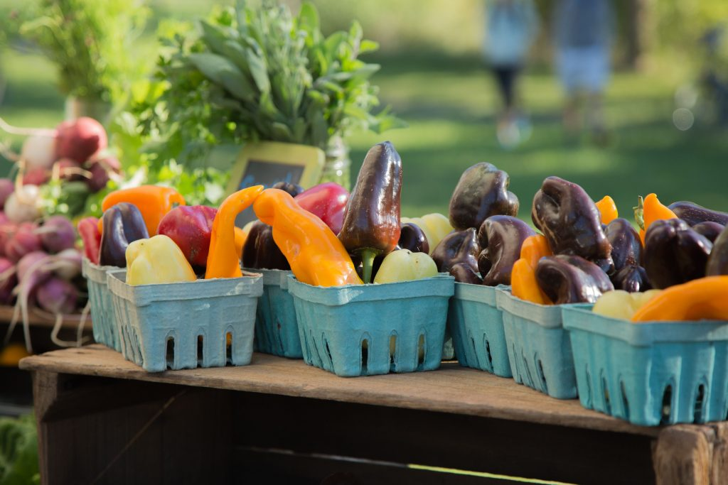 blue quart bins filled with multi-color peppers on a wooden bin at a Delaware farmers' market